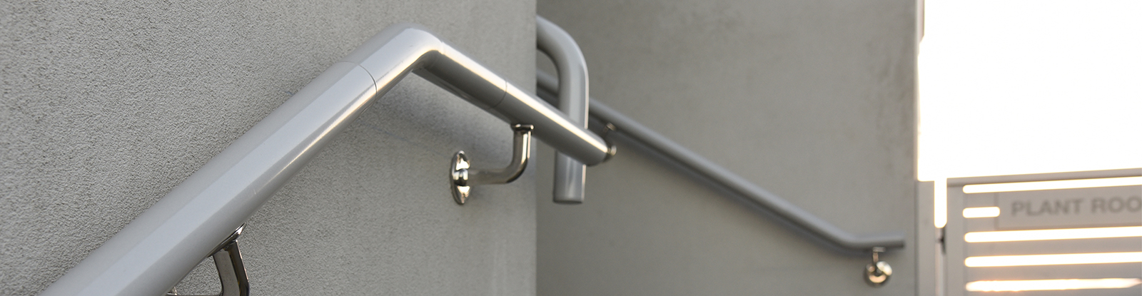 Brushed aluminium handrail fixed to concrete wall